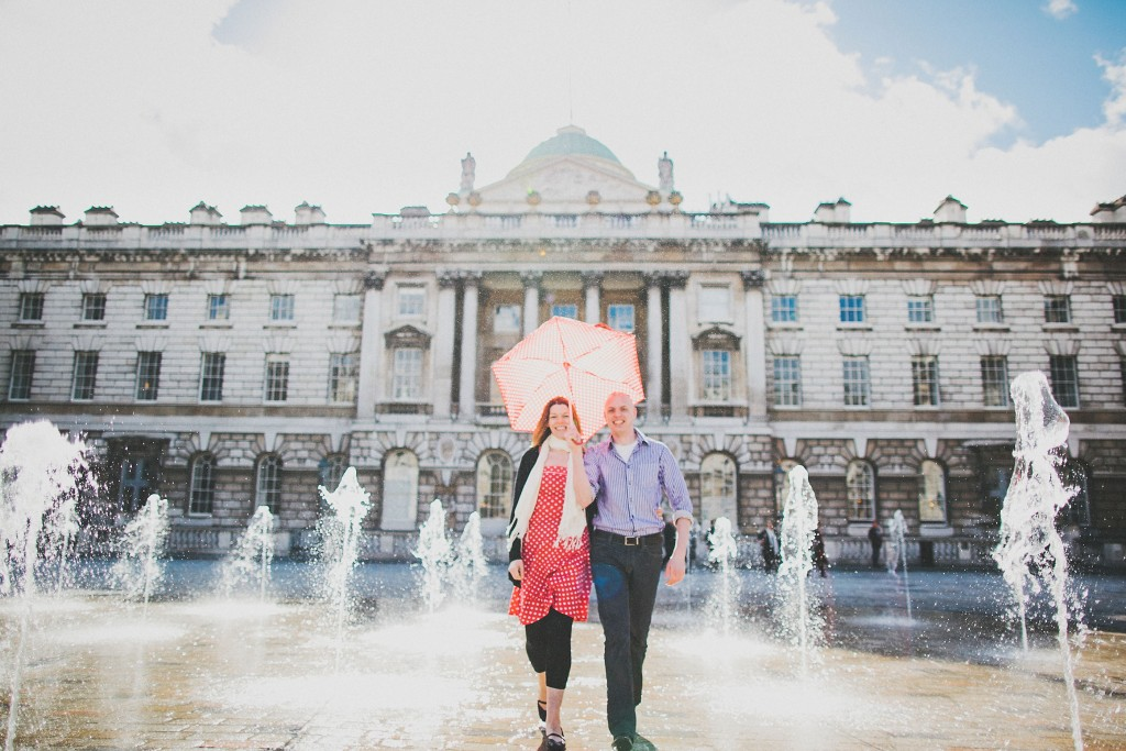 nicholas-lau-nicholau-lincolns-inns-fields-somerset-house-engagement-couple-photos-prewedding-love-london-fine-art-photography-playing-in-fountains-umbrella-parasol-red-polka-dot-in-the-sun