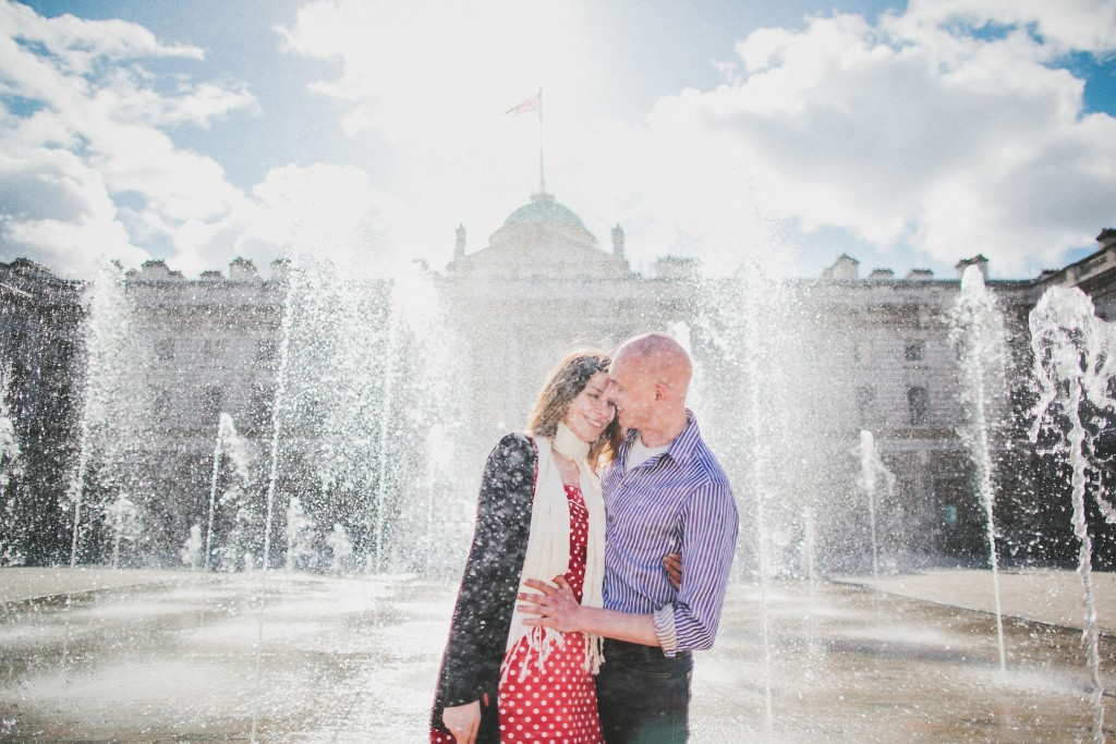 nicholas-lau-nicholau-lincolns-inns-fields-somerset-house-engagement-couple-photos-prewedding-love-london-holding-smiling-getting-wet-fountains-sun-flare-endearing
