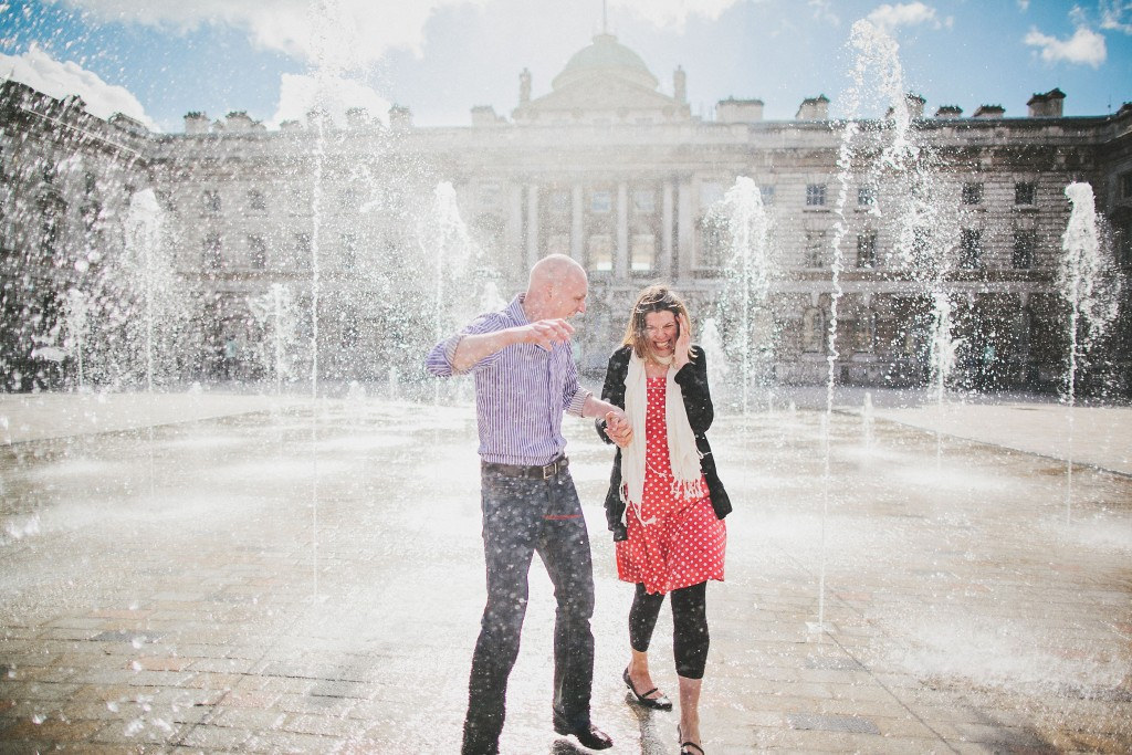 nicholas-lau-nicholau-lincolns-inns-fields-somerset-house-engagement-couple-photos-prewedding-love-london-playing-laughing-getting-splashed-wet-holding-hands-red-polka-dot-dress-cardigan-blue