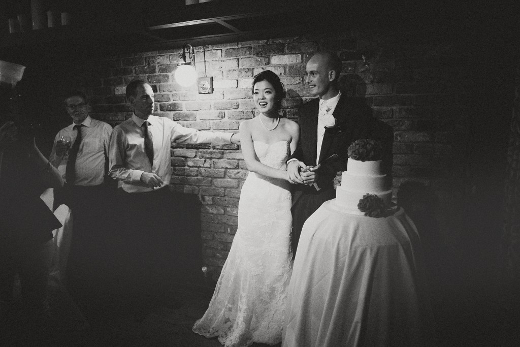nicholau-nicholas-lau-interracial-wedding-black-and-white-cut-the-cake-urban-reception-pub-bricks