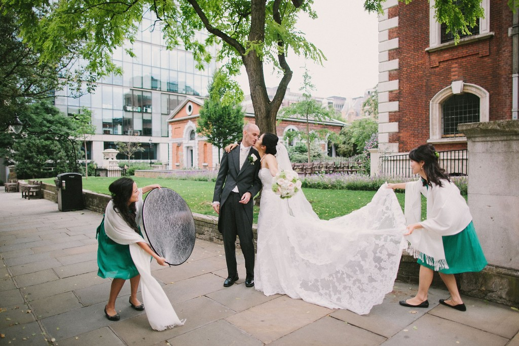 nicholau-nicholas-lau-interracial-wedding-bridesmaid-spreading-veil-holding-light-reflector-kissing-groom-and-bride-behind-the-scenes