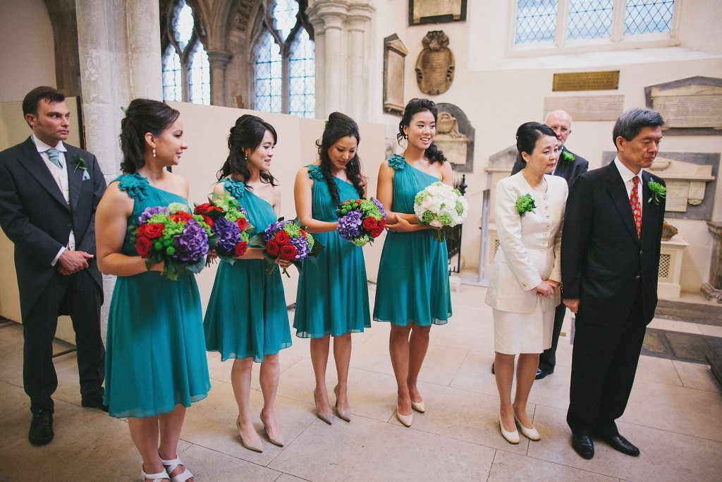 nicholau-nicholas-lau-interracial-wedding-bridesmaids-hold-colourful-bouquets-nude-heels-one-shoulder-teal-dresses