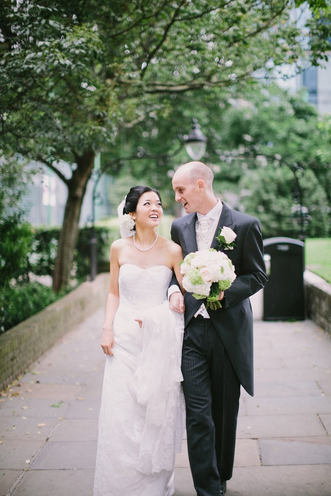 nicholau-nicholas-lau-interracial-wedding-groom-holds-bride-and-bouquet-charming-garden-stroll