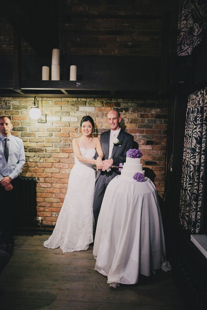 nicholau-nicholas-lau-interracial-wedding-reception-cut-the-cake-three-tiered-cake-purple-and-white-urban-bricks