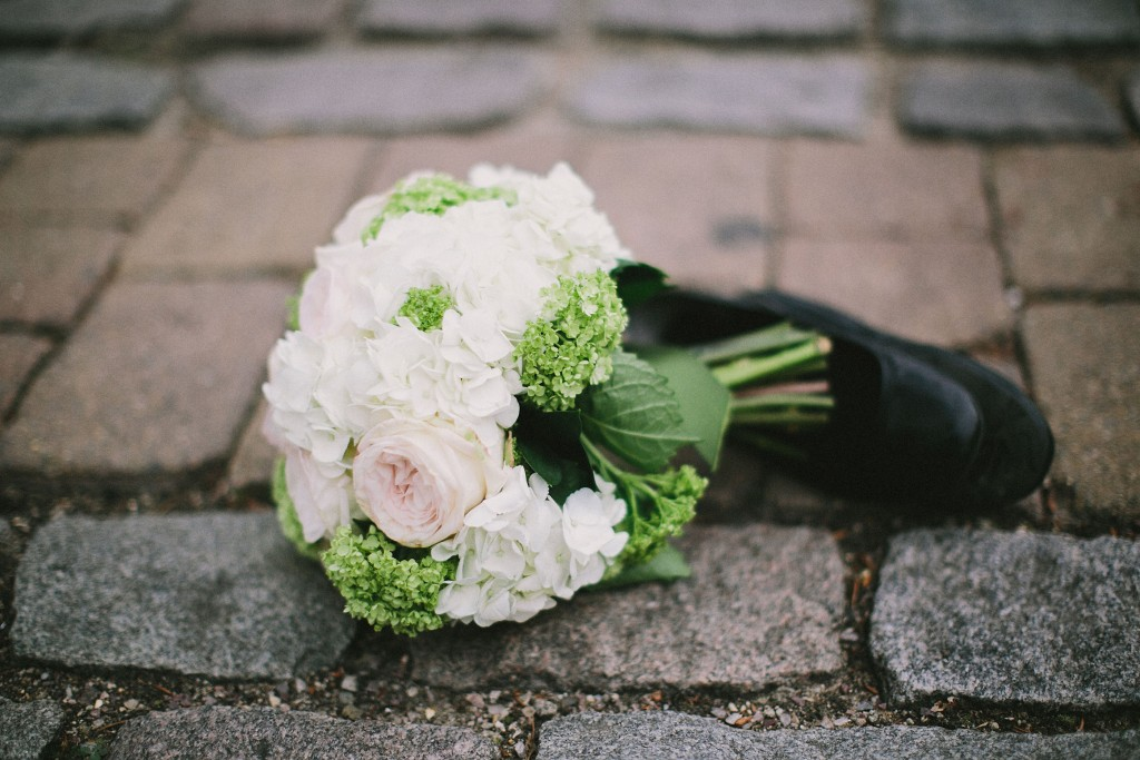 nicholau-nicholas-lau-interracial-wedding-shoe-and-a-bouquet-on-the-ground-white-roses-cobblestones