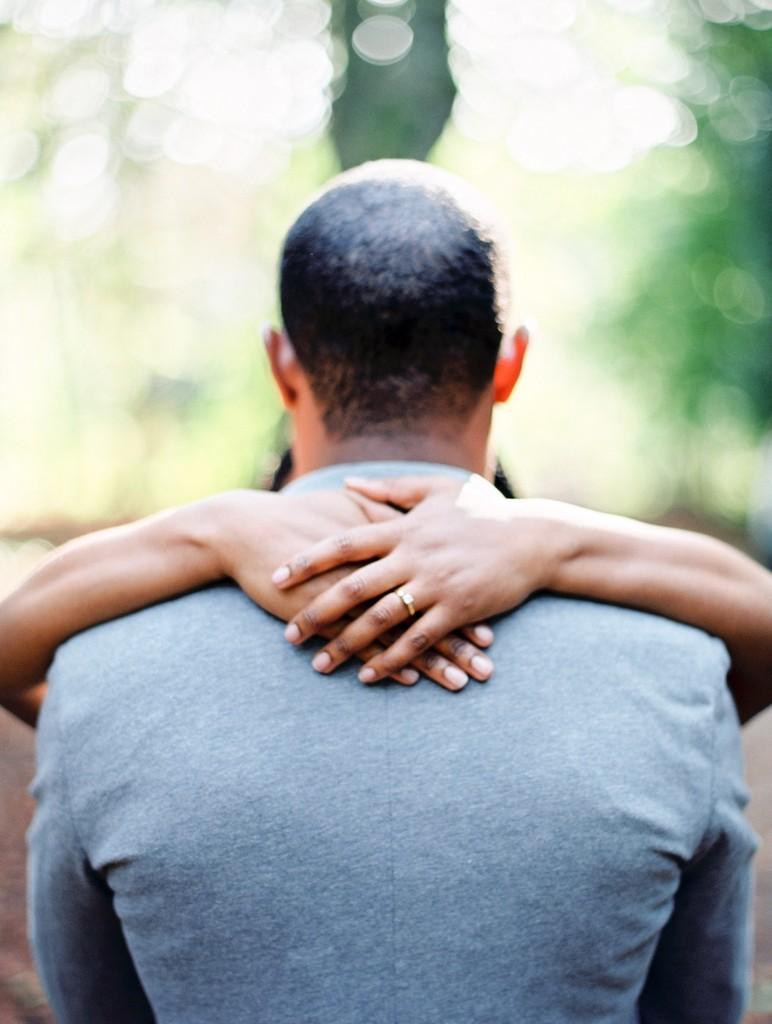 nicholau-nicholas-lau-photography-couples-session-pre-wedding-engagement-love-african-london-grey-suit-blazer-holding-hugging-kissing-diamond-ring-symmetrical-hands-his-shoulders