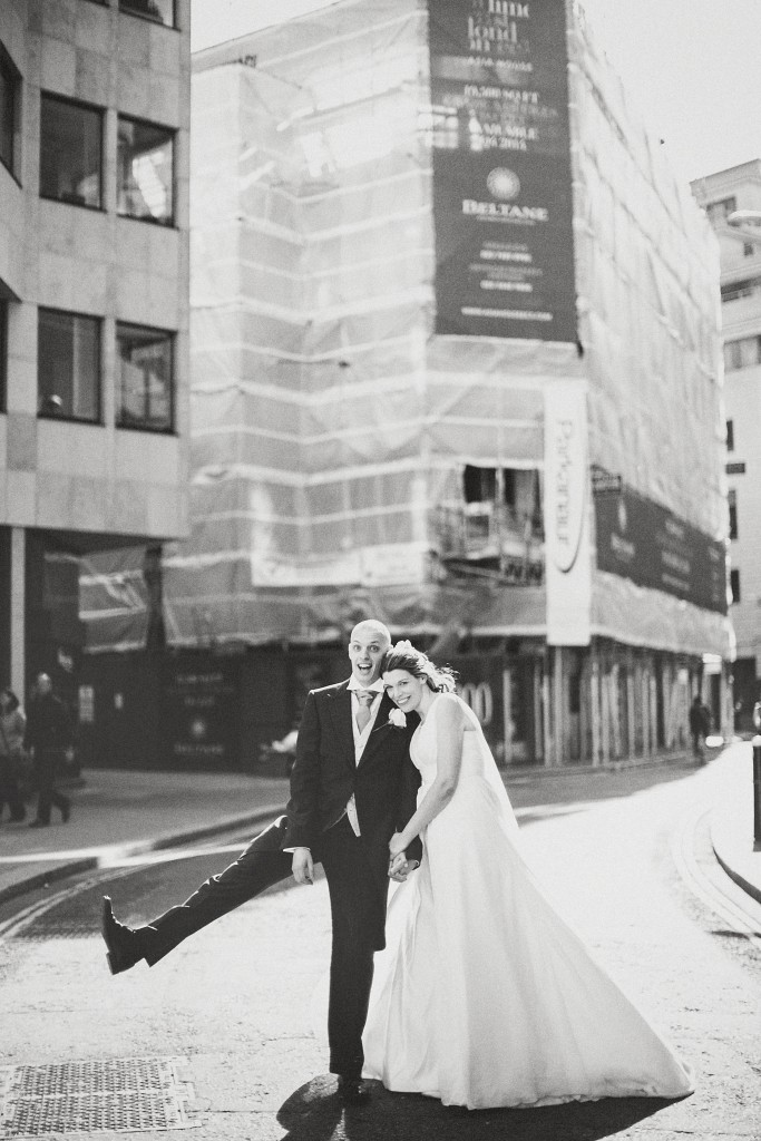 nicholas-lau-nicholau-london-weddings-fine-art-photography-leadenhall-market-st-helens-church-documentary-style-black-white-groom-leg-out-quirky-dance