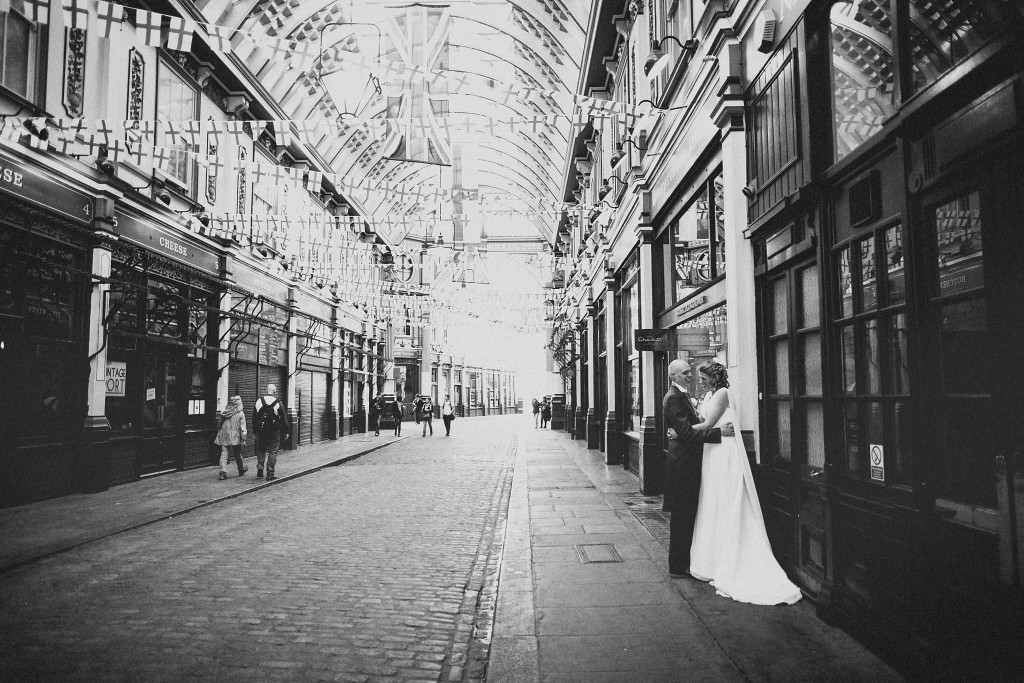 nicholas-lau-nicholau-london-weddings-fine-art-photography-leadenhall-market-st-helens-church-documentary-style-cape-dress-holding-jolly-roger