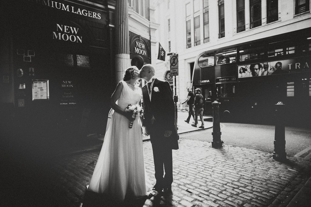 nicholas-lau-nicholau-london-weddings-fine-art-photography-leadenhall-market-st-helens-church-documentary-style-white-black-dress-groom-kiss-bride-doubledecker-bus