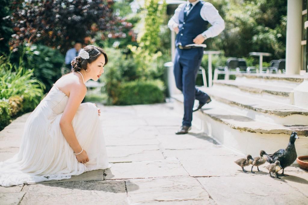 nicholau-nicholas-lau-wedding-fine-art-photography-london-chinese-asian-bride-playing-with-ducks-ducklings-groom-jogs-trots-kensington-roof-gardens