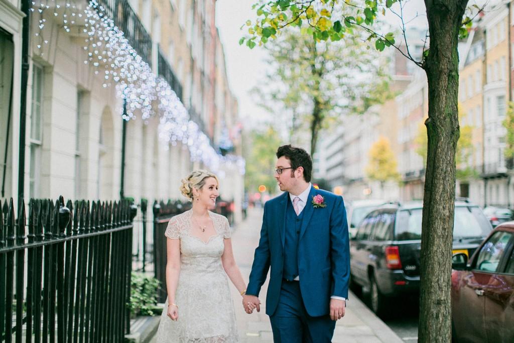 nicholas-lau-nicholau-wedding-photography-photographer-fine-art-film-winter-christmas-london-UK-modern-unique-the-arch-asia-house-holding-hands-sidewalk-blue-suit-white-dress-knee-length