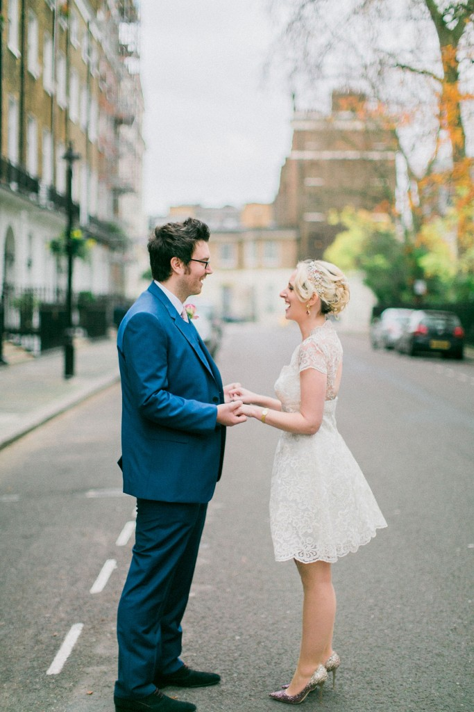 nicholas-lau-nicholau-wedding-photography-photographer-fine-art-film-winter-christmas-london-UK-modern-unique-the-arch-asia-house-holding-hands-standing-together-blue-suit-white-knee-length-dress
