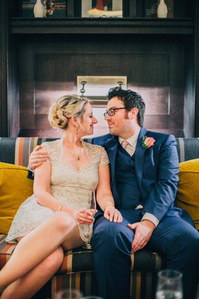 nicholas-lau-nicholau-wedding-photography-photographer-fine-art-film-winter-christmas-london-UK-modern-unique-the-arch-asia-house-yellow-couch-bride-groom-sitting-blue-suit-knee-length-dress