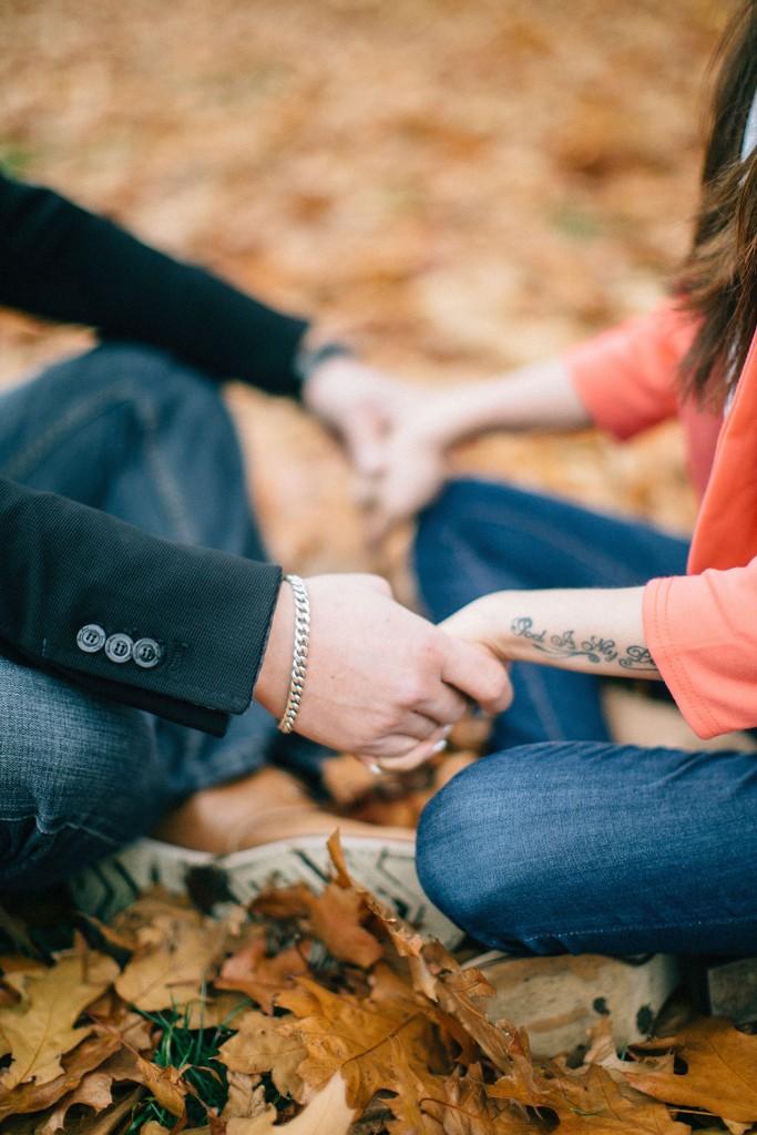 nicholau-nicholas-lau-couple-pre-wedding-film-fine-art-photography-red-blazer-leaves-fall-autumn-kew-gardens-uk-london-sitting-cross-legged-holding-hands-ring-tattoo