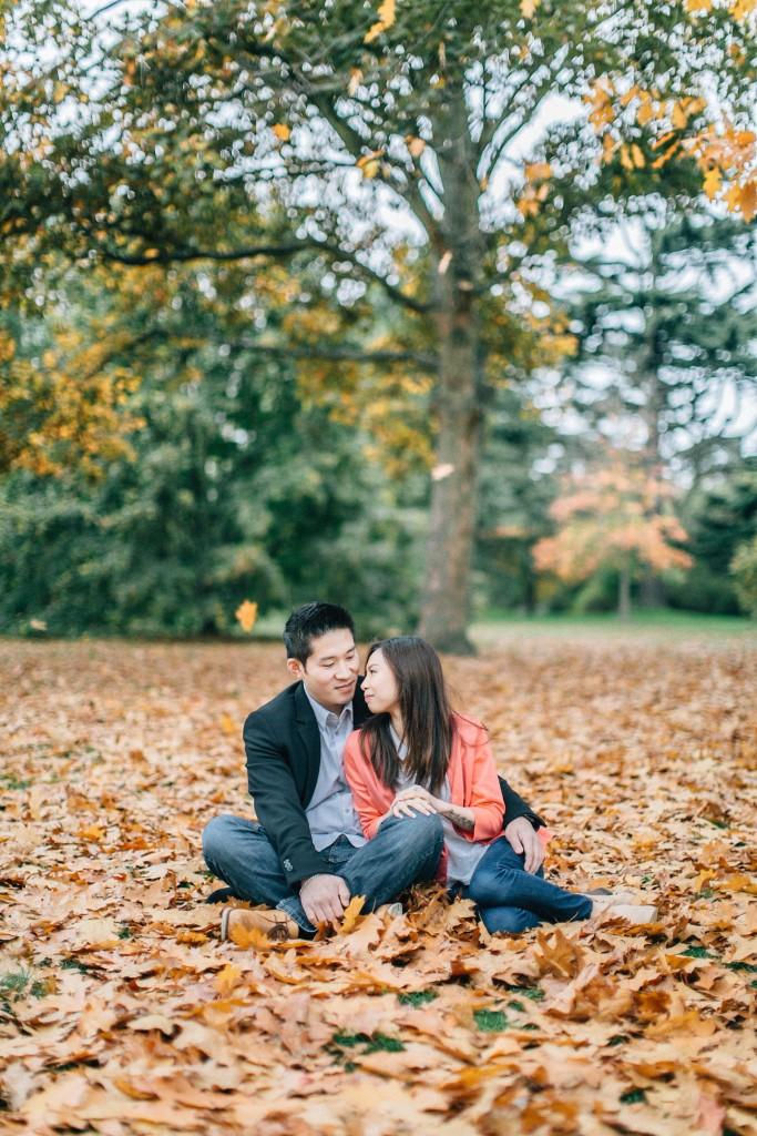 nicholau-nicholas-lau-couple-pre-wedding-film-fine-art-photography-red-blazer-leaves-fall-autumn-kew-gardens-uk-london-sitting-cuddling-together-trees-pile